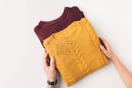 Photo for Cropped view of couple hands with knitted burgundy and yellow sweaters, isolated on white - Royalty Free Image