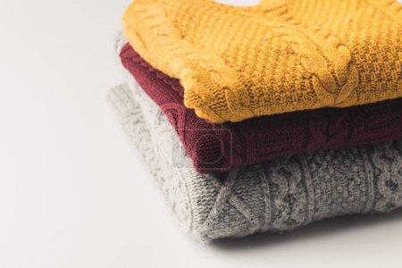 Foto de Montón de suéteres acogedoras cálidos, aislado en blanco - Imagen libre de derechos
