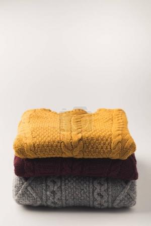 Photo for Pile of warm cozy sweaters,  isolated on white - Royalty Free Image