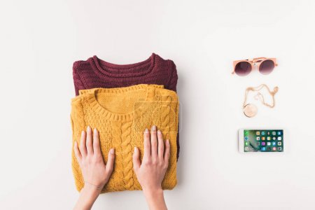 hands with sweaters and iphone