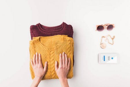 Photo for Cropped view of female hands with sweaters, sunglasses and smartphone with facebook messenger appliance, isolated on white - Royalty Free Image