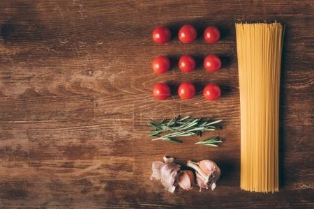 flat lay with row pasta, tomatoes, rosemary and garlic on wooden table