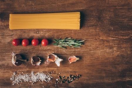 flache Lage mit Reihennudeln und frischen Zutaten auf Holztisch