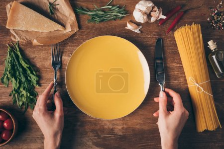 cropped view of hands with knife and fork at plate with row pasta and fresh ingredients around on wooden table