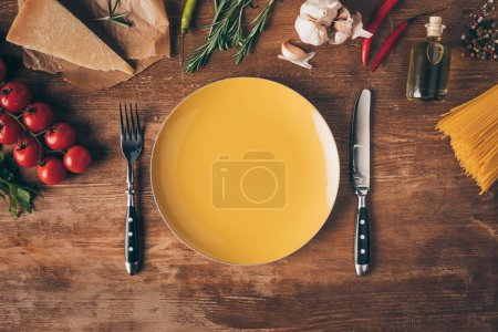 top view of row pasta, fresh ingredients and plate with knife and fork on wooden tabletop