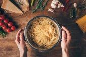 """Постер, картина, фотообои """"вид сверху рук с Макароны спагетти и ингредиенты на деревянные настольные"""""""