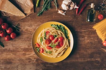 Photo for Top view of traditional italian pasta with tomatoes and arugula in plate on wooden table with ingredients - Royalty Free Image