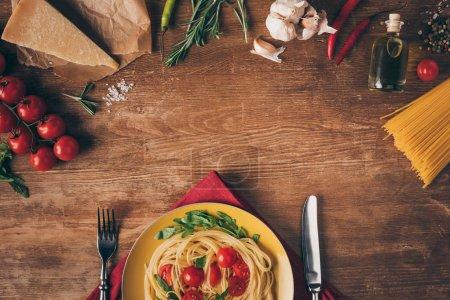 Photo pour Vue de dessus de pâtes italiennes traditionnelles avec les tomates et la roquette en plaque sur une table en bois avec des ingrédients - image libre de droit