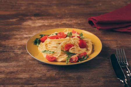 Photo for Traditional italian pasta with tomatoes and arugula in plate on wooden tabletop - Royalty Free Image