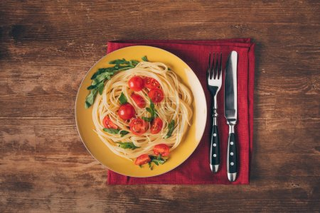 Photo for Traditional italian pasta with tomatoes and arugula in plate with knife and fork on wooden tabletop - Royalty Free Image