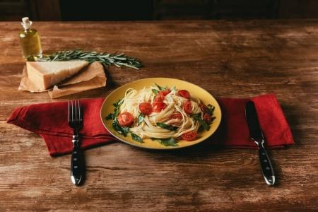 Photo for Traditional pasta with tomatoes and arugula in plate on table with Parmesan and rosemary - Royalty Free Image