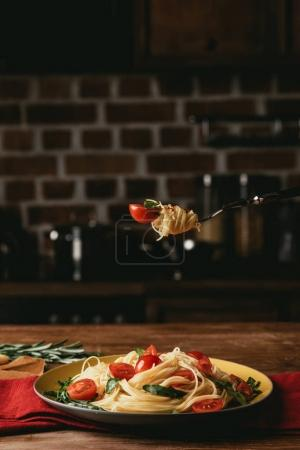 Photo for Traditional italian pasta with tomatoes and arugula on fork - Royalty Free Image