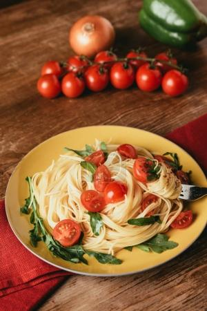 delicious italian pasta with tomatoes and arugula in plate