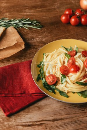 traditional italian pasta with tomatoes and arugula in plate