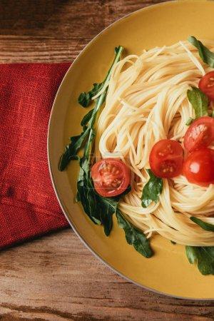 Photo pour Vue de dessus de pâtes italiennes traditionnelles avec les tomates et la roquette en plaque - image libre de droit
