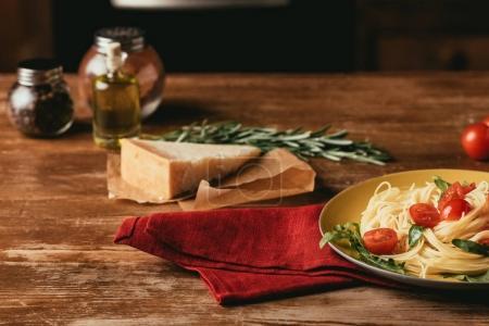 Photo pour Pâtes italiennes traditionnelles avec les tomates et la roquette en plaque sur une table en bois avec du Parmesan, romarin et huile - image libre de droit