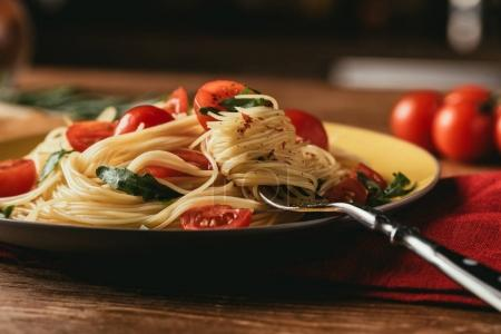 Photo for Traditional italian pasta with tomatoes and arugula in plate - Royalty Free Image