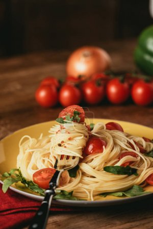 Photo for Traditional italian pasta with tomatoes and arugula in plate with fork - Royalty Free Image