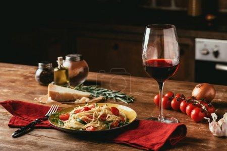 Photo pour Pâtes italiennes traditionnelles avec les tomates et la roquette dans l'assiette et le verre de vin rouge - image libre de droit