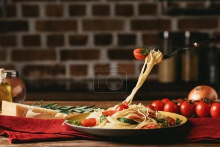 Photo pour Pâtes italiennes traditionnelles avec des tomates et roquette sur fourche - image libre de droit