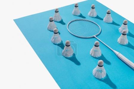 Foto de Vista de ángulo alto de la raqueta de bádminton y volantes en papel azul, aislado en blanco - Imagen libre de derechos
