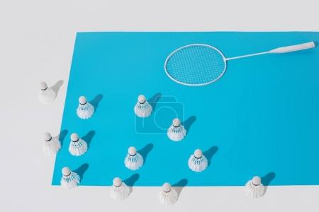 high angle view of white badminton racket and shuttlecocks on blue paper