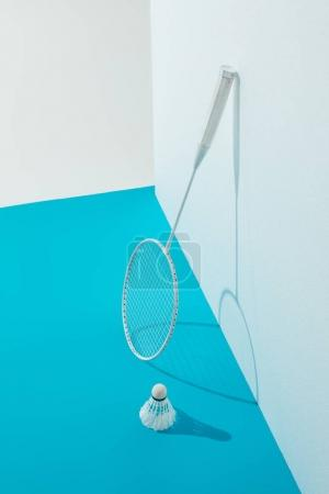badminton racket and shuttlecock on blue paper near white wall
