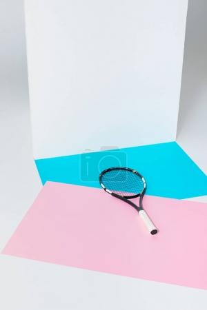 tennis racket lying on blue and pink papers at white wall