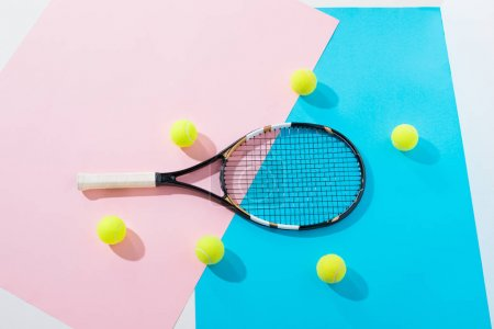 top view of tennis racket and balls on blue and pink papers