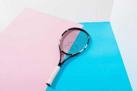 tennis racket lying on blue and pink papers