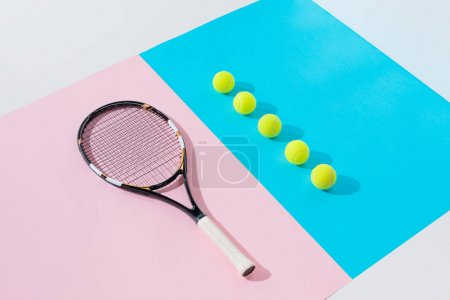 tennis racket on pink and yellow balls in row on blue