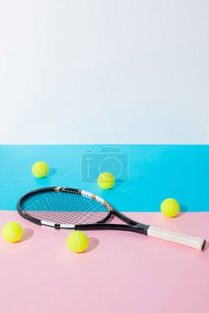 tennis racket and yellow balls on blue and pink papers with copy space