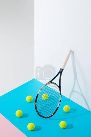 circle of tennis balls on blue around tennis racket at white wall