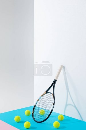 circle of tennis balls on blue around tennis racket at white wall with copy space