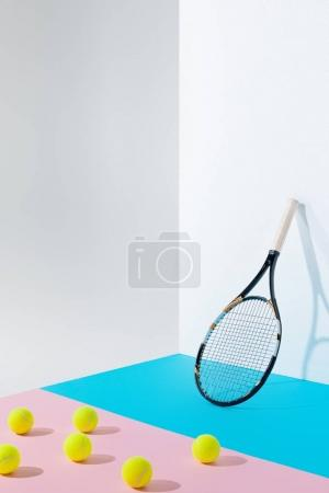 yellow tennis balls on pink paper and tennis racket on blue at white wall with copy space