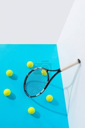 high angle view circle of tennis balls around tennis racket on blue at white wall