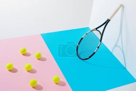 yellow tennis balls on pink paper and tennis racket on blue at white wall