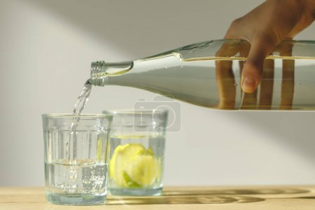 cropped image of woman pouring water into transparent glass