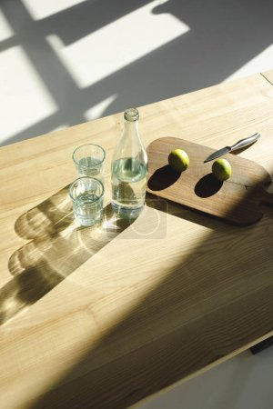 overhead view of limes on wooden board and water in glasses and bottle on wooden table