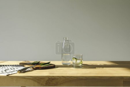 cut cucumbers and detox water on wooden table