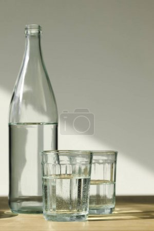 transparent bottle and glasses with mineral water on wooden table