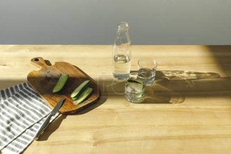 overhead view of cut cucumbers and bottle with water on wooden table