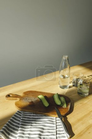 overhead view of cut cucumbers and antioxidant water on wooden surface