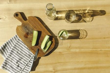 Photo for Top view of cut cucumbers and antioxidant water on wooden surface - Royalty Free Image
