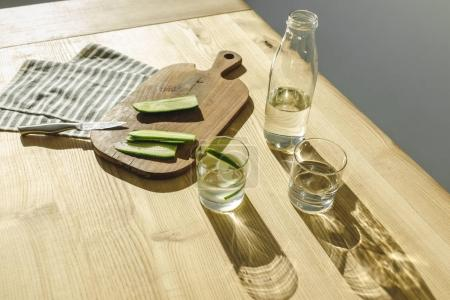 overhead view of cut cucumbers on wooden board and glasses with detox water on wooden surface