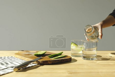 cropped image of woman pouring water into glasses with cucumbers