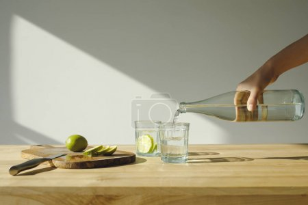 cropped image of woman pouring mineral water into glass