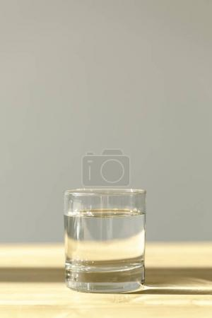 transparent glass with calm mineral water on wooden table