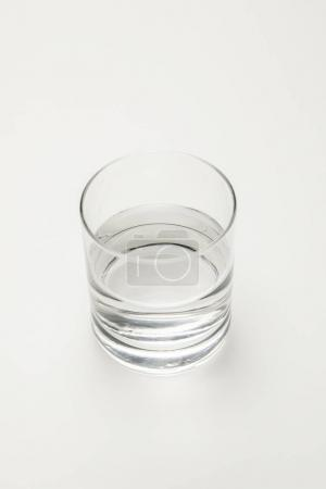 overhead view of transparent glass with calm mineral water isolated on white
