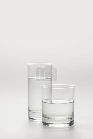 two different glasses with calm water isolated on white